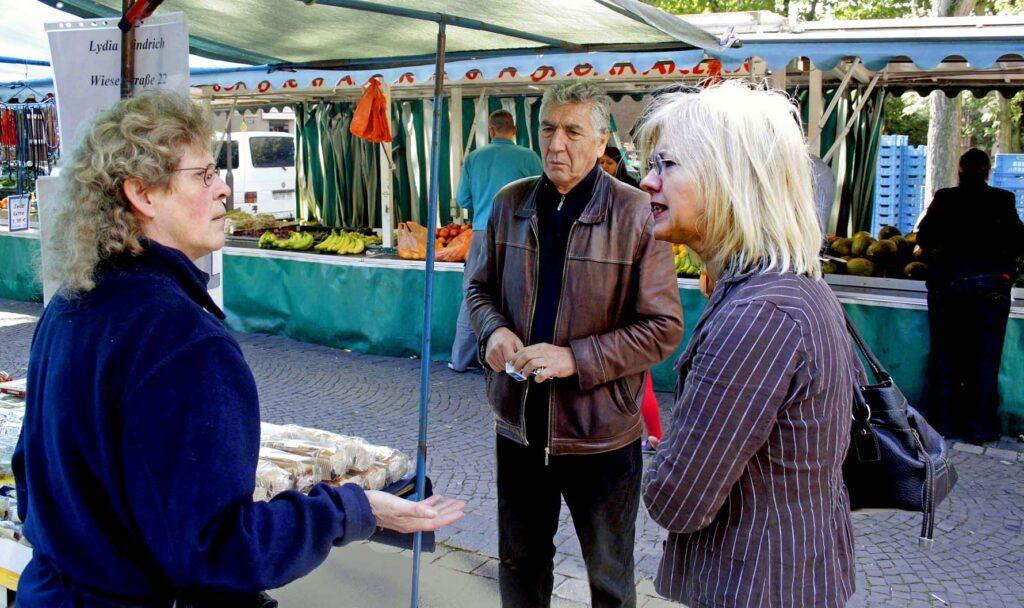 Markthändlerin Lydia Windrich unterhält sich mit deutsch-türkischem Paar
