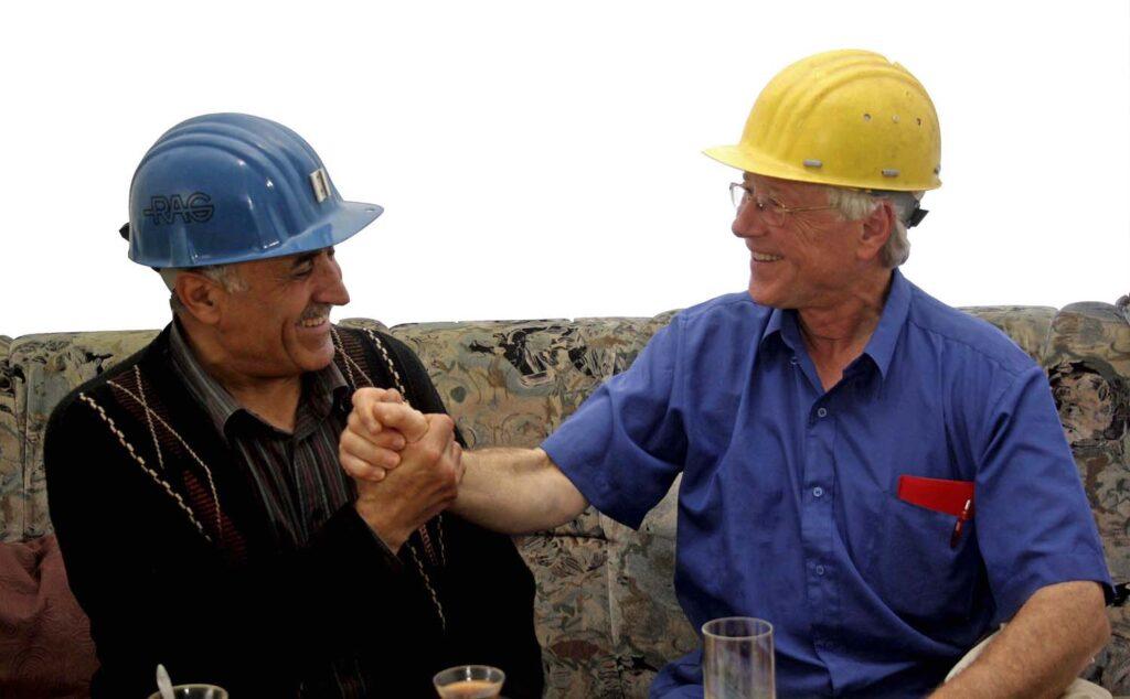 Deutscher Bergarbeiter gibt seinem türkischen Kumpel die Hand.
