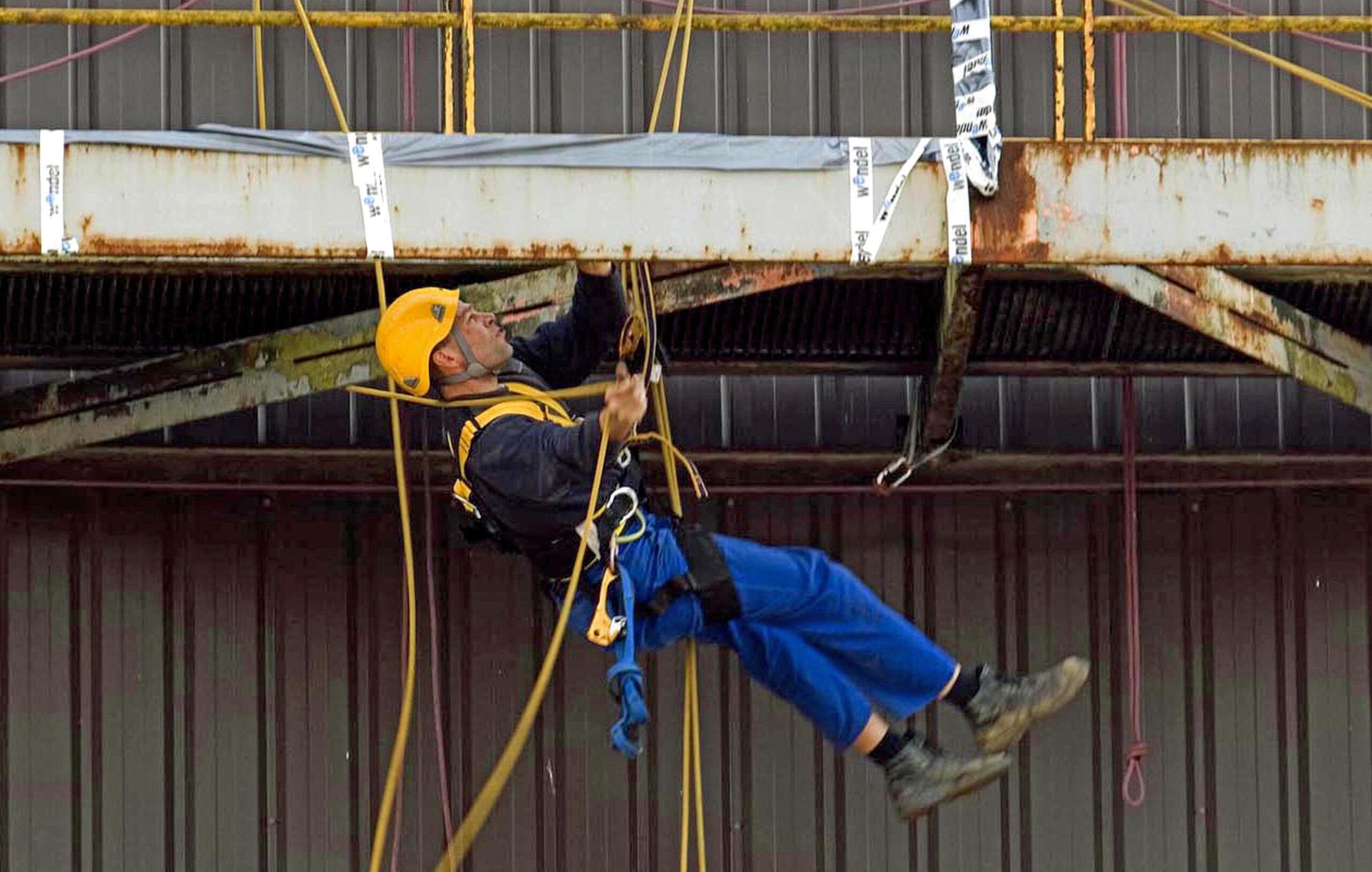 Industriekletterer hängt mit Seilen an Wand.