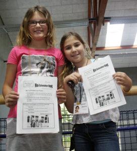 Zwei Kinder zeigen eigene Zeitung